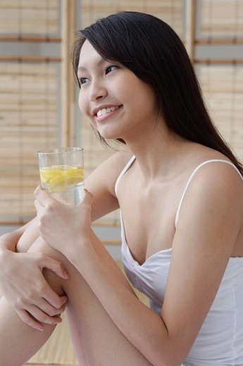 Young woman holding glass of water, hugging knees, looking away : Stock Photo