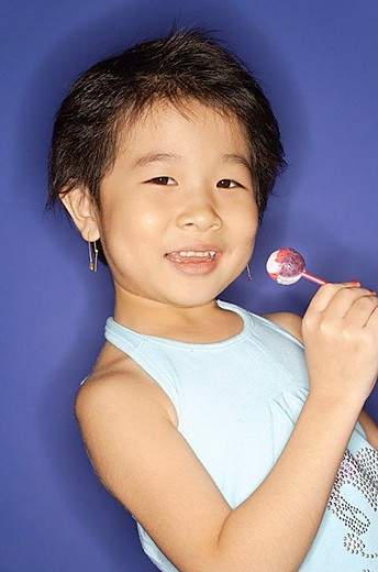 Young girl holding lollypop, smiling : Stock Photo