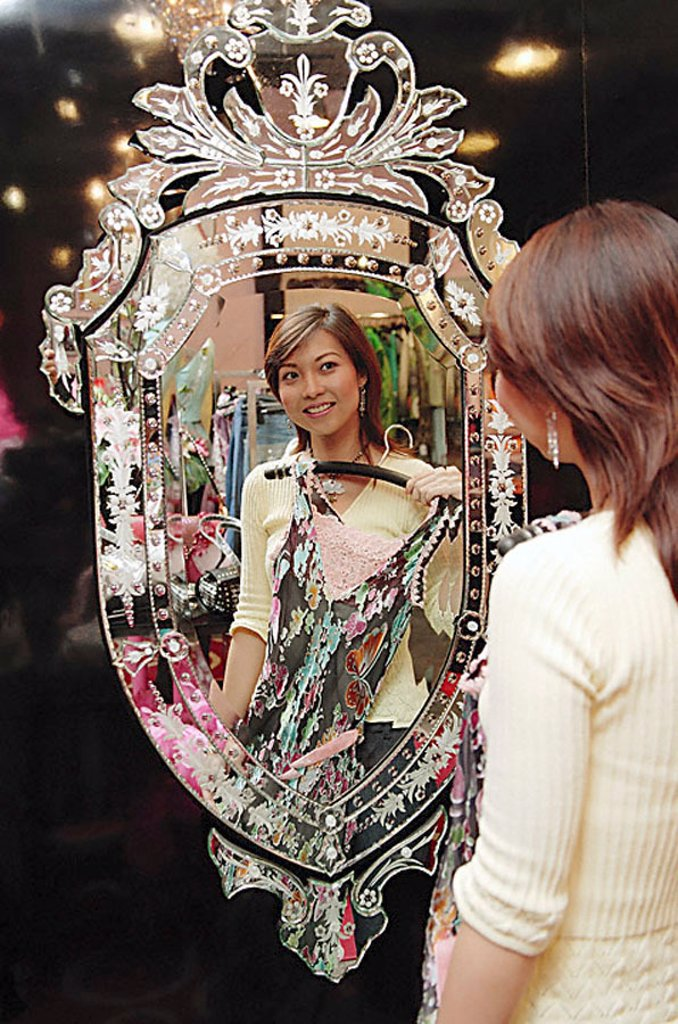 Woman in clothing store, holding dress, looking at mirror : Stock Photo