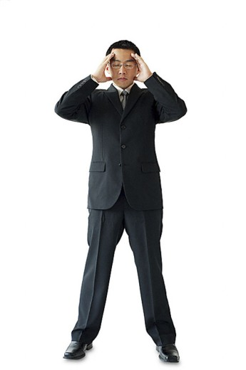 Businessman standing with hands on head : Stock Photo