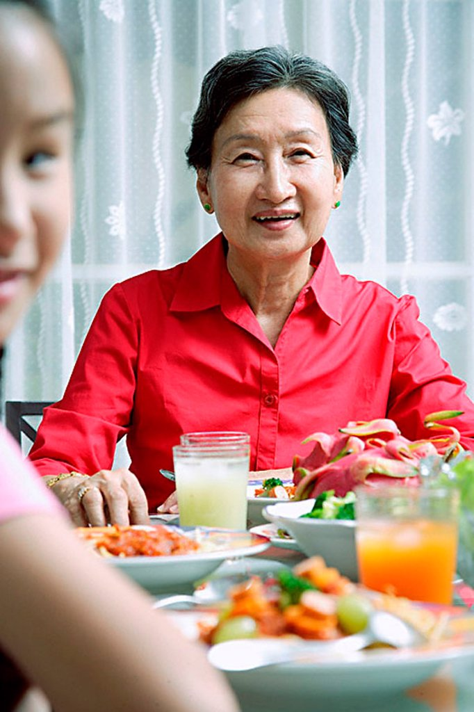 Senior adult at dining table, smiling at camera, granddaughter in the foreground : Stock Photo