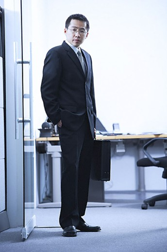 Businessman standing, looking at camera, portrait : Stock Photo