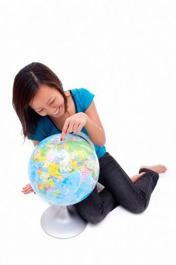 Woman pointing at globe : Stock Photo