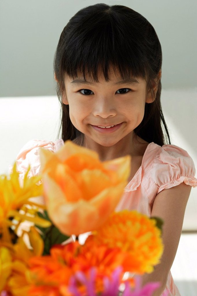 Girl with flowers smiling at camera : Stock Photo