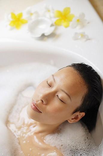 Stock Photo: 4079R-3261 Woman in bathtub, eyes closed, head shot