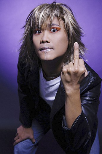 Man in leather jacket and face paint, making rude hand gesture : Stock Photo