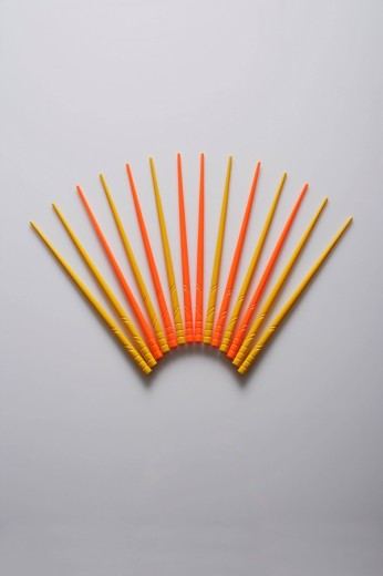 Orange and yellow chopsticks in the shape of a fan. : Stock Photo
