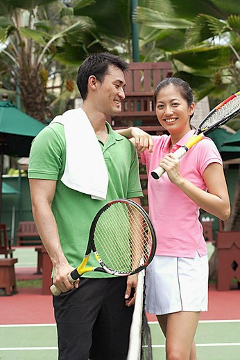 Stock Photo: 4079R-3532 Man and women standing on tennis court with tennis rackets