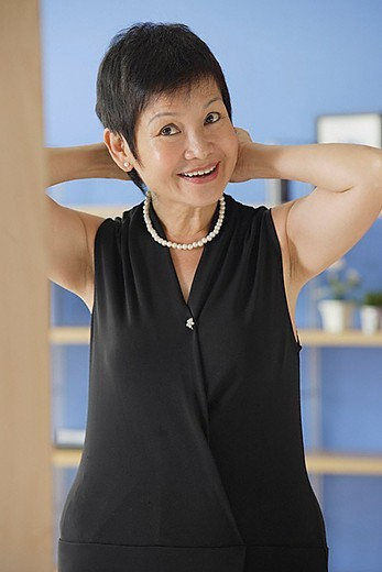 Mature woman putting on pearl necklace : Stock Photo