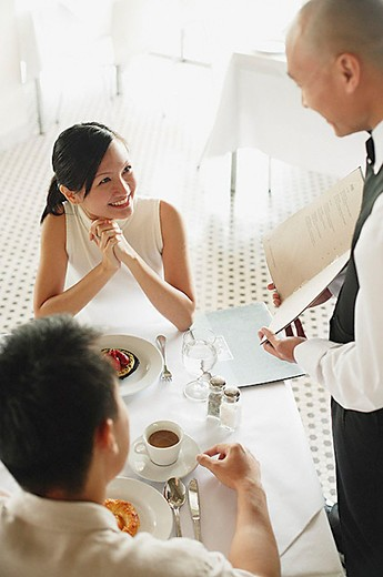 Waiter showing menu to couple at restaurant, woman smiling at him : Stock Photo