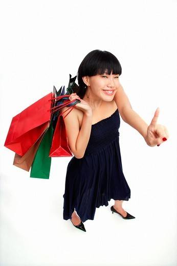 Young woman carrying shopping bags, pointing finger : Stock Photo