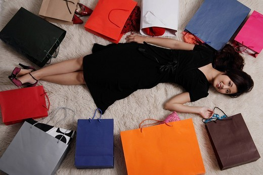 Chinese woman laying on floor with shopping bags : Stock Photo