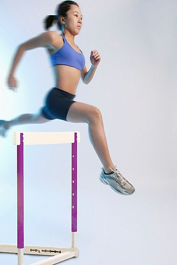 Stock Photo: 4079R-4461 Woman jumping over hurdle