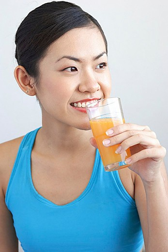 Woman holding glass orange juice to mouth, looking away : Stock Photo