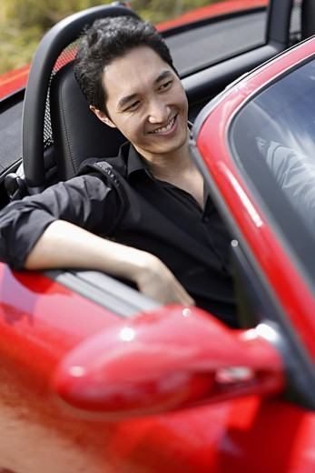 Stock Photo: 4079R-4564 Man sitting in red convertible car, smiling
