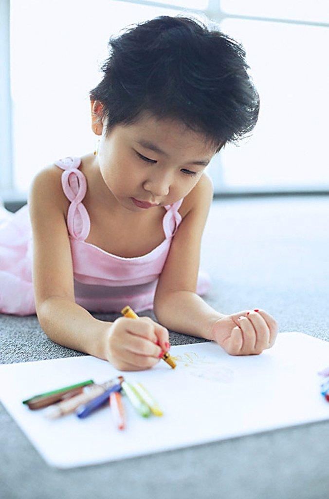 Young girl lying on floor, drawing : Stock Photo