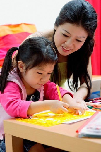 Stock Photo: 4079R-4649 Mother and young daughter drawing at home
