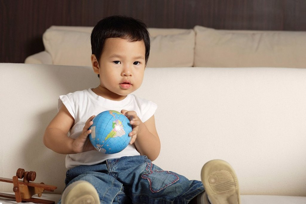 Stock Photo: 4079R-4860 Baby boy holding globe looking at camera