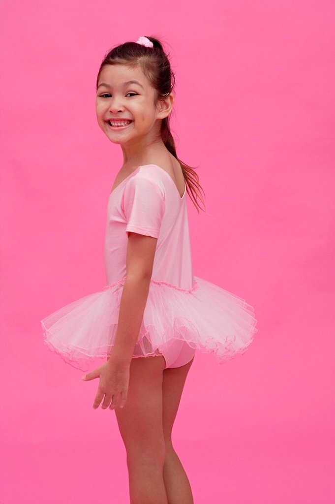 Stock Photo: 4079R-5085 Young girl in ballet outfit, turning to smile at camera