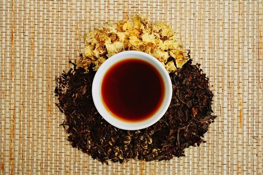 Chinese teacup and pile of loose tea leaves, directly above : Stock Photo
