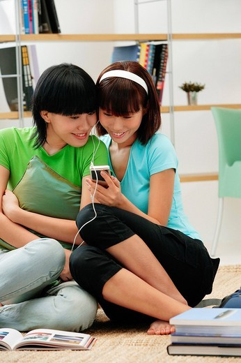 Stock Photo: 4079R-5212 Young women wearing earphones, listening to MP3 player