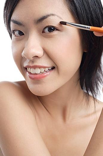 Woman holding brush, applying eyeshadow : Stock Photo