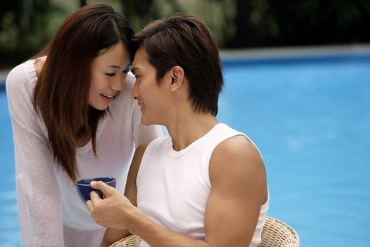 Young couple touching foreheads poolside : Stock Photo
