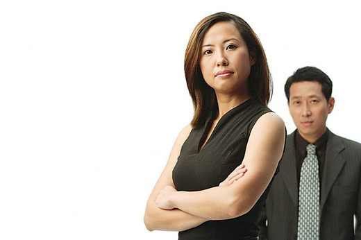 Woman with arms crossed, looking at camera, man behind her : Stock Photo