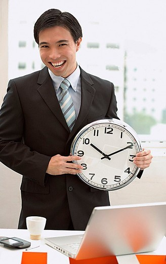 Businessman standing in front of desk, holding clock : Stock Photo