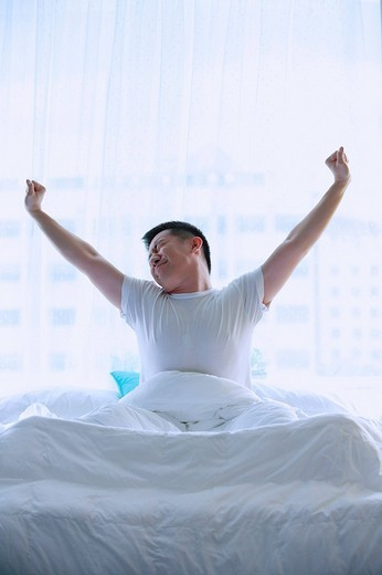 Stock Photo: 4079R-6072 Man in bed, stretching