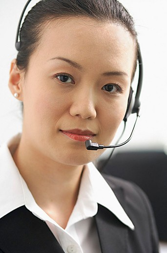 Executive with headset, looking at camera : Stock Photo