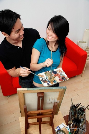 Couple in front of painting easel, looking at each other, high angle view : Stock Photo