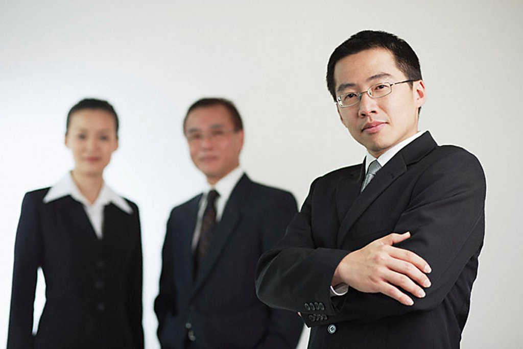 Young businessman with arms crossed, businessman and businesswoman in the background : Stock Photo