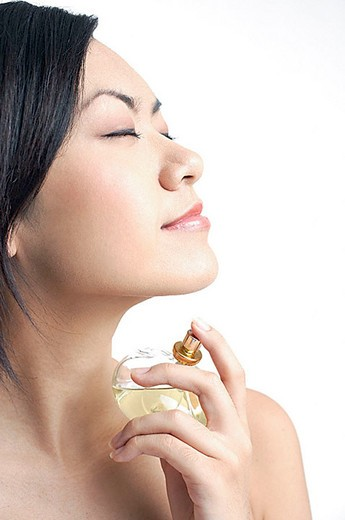 Woman applying perfume, sideview : Stock Photo