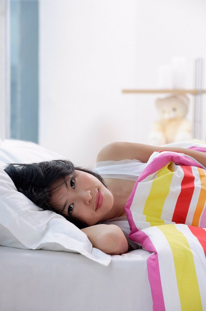 Stock Photo: 4079R-6869 Young woman lying on bed, looking at camera