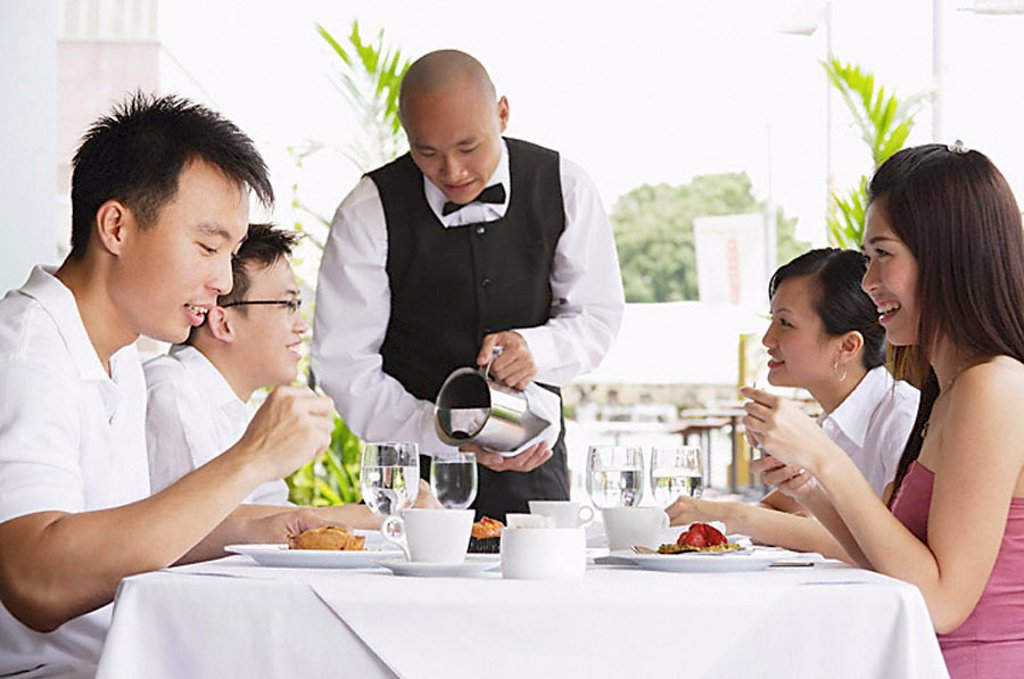 Stock Photo: 4079R-6883 Group of friends at restaurant eating, waiter pouring water at their table