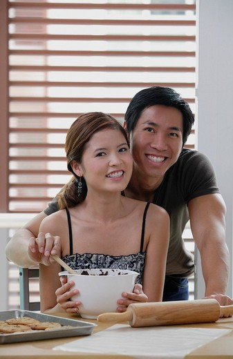 Couple in kitchen, smiling at camera : Stock Photo