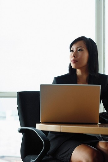Businesswoman sitting at desk with laptop, looking away : Stock Photo