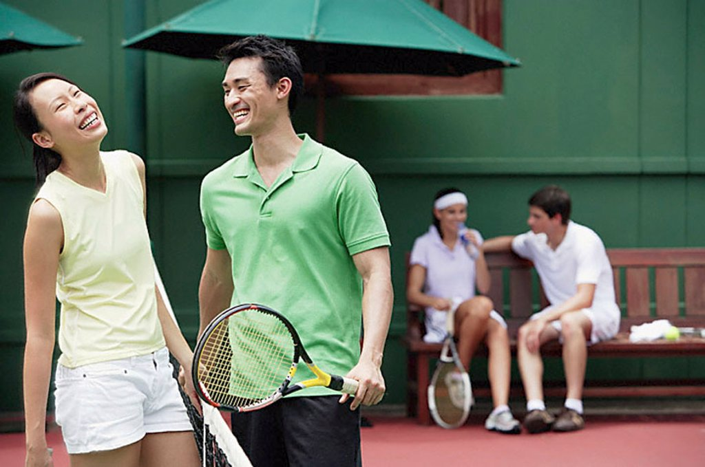Couples spending time together on tennis court, laughing : Stock Photo