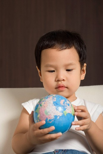 Stock Photo: 4079R-7369 Baby boy looking at globe
