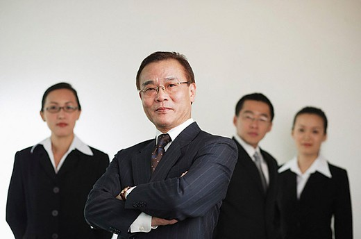 Businessman with arms crossed, people in the background : Stock Photo