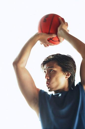 Stock Photo: 4079R-7601 Man aiming basketball, concentrating