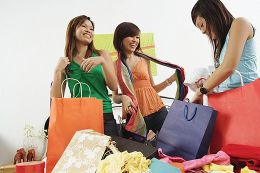 Three girls in bedroom, looking at clothes from shopping bags : Stock Photo