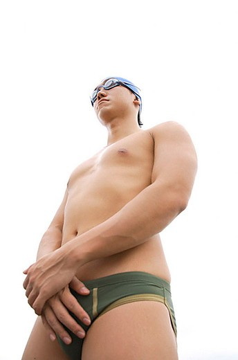 Stock Photo: 4079R-7630 Young man with swim cap and goggles, hands clasped