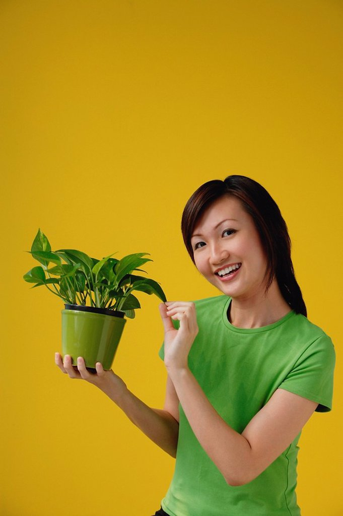 Stock Photo: 4079R-7648 Young Woman with houseplant, smiling at camera