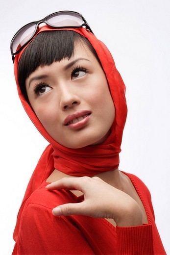 Portrait of woman wearing red sweater, scarf and sunglasses : Stock Photo