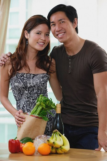 Couple smiling at camera, fresh fruits and vegetables on table in front of them : Stock Photo