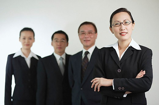 Businesswoman with arms crossed, other executives in the background : Stock Photo