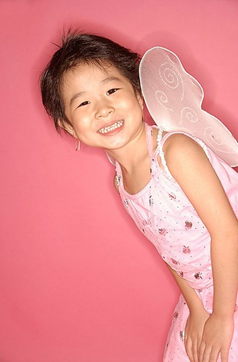 Young girl in pink dress with artificial wings, smiling at camera : Stock Photo