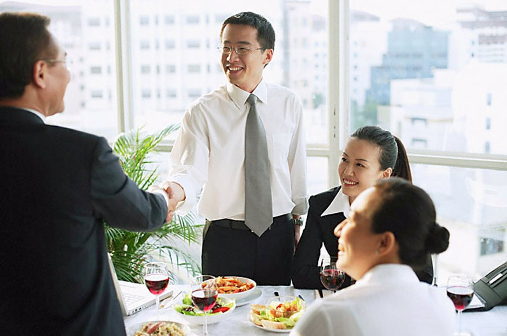Businessmen shaking hands over lunch table, businesswomen sitting next to them : Stock Photo